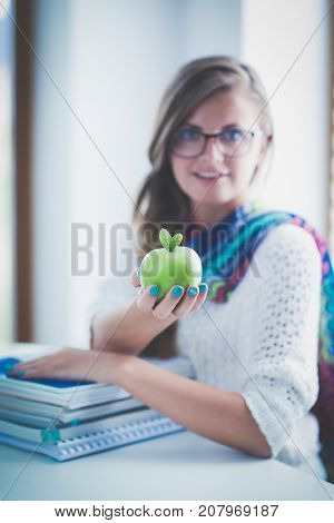 Female college students sitting on the desk with apple on a pile of books. Student. College