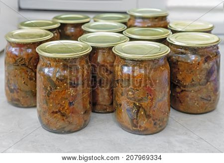 Home canning: small glass bottles with canned vegetables which were closed with metal lids.