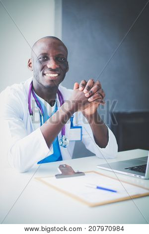 Portrait of young male doctor wearing headset while using computer at desk in clinic. Doctor.