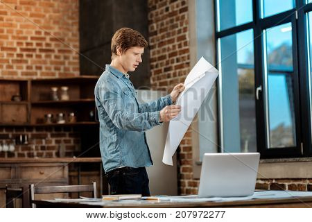 Thoroughly studying. Pleasant young engineer standing in the study, holding a big blueprint and scrutinizing it