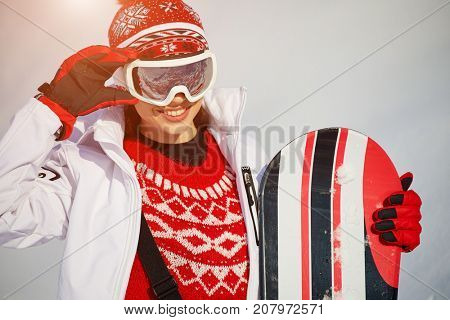 Sport woman  snowboarder on snow over winter resort