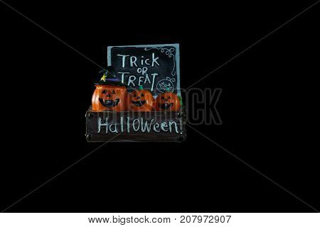 Halloween concept : Low key image of ceramic pumpkins Halloween and trick or treat sign isolated on black background