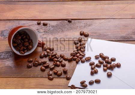 Get enough sleep from a mug grain coffee. coffee grains get out of the cup over paper and broun wooden background