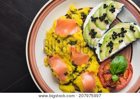 Scramble With Avocado, Tomatoes And Pieces Of Salmon