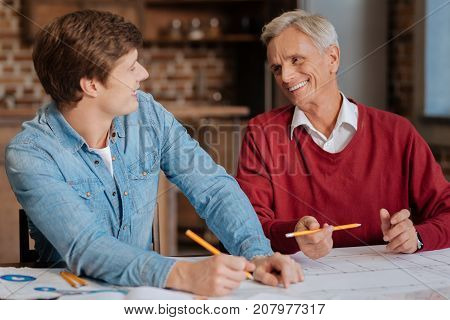 Pleasant cooperation. Handsome young engineer sitting at the table next to his senior colleague and chatting with him while drawing a blueprint together