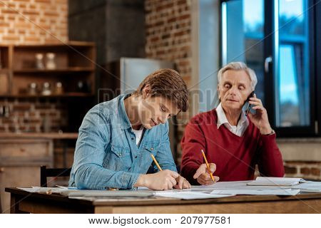 Crucial instructions. Pleasant senior man sitting at the table next to his young colleague, talking on the phone while pointing at the places in blueprint needing corrections