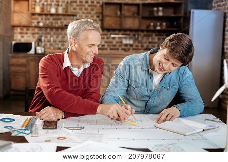 Vital suggestion. Caring senior mentor sitting at the table next to his young colleague drawing a blueprint and suggesting a correction in it to him