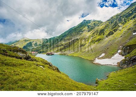 Mountain lake. The lake between the rocks. Beautiful sky with clouds. Wonderful valley. Eastern Europe. Romania.Lake Balea. Typical alpine house on mountain lake. Beautiful blue sky with clouds.