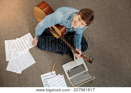 Happy musician. The top view of a charming young man sitting on the floor surrounded with musical scores, holding a guitar and smiling at the camera