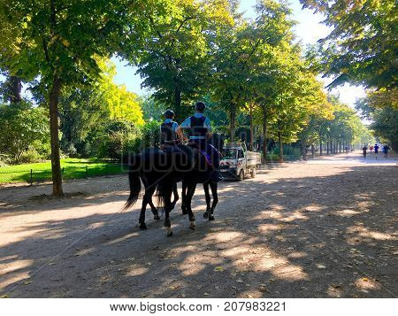 Paris France, 23 September 2017: French Mounted police keeps order in Champs de Mars park with people running in background in Paris
