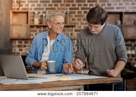 Vital help. Pleasant senior mentor holding a cup of coffee and helping his young colleague draw a blueprint by pointing at a place requiring correction