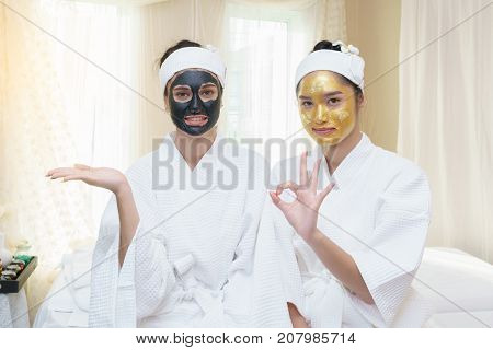 Beautiful young Asian woman having high quality and authentic pure gold facial mask and pointing her finger to her friend who having facial mud mask and open her hands for concept placing a sign.