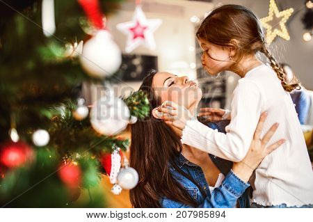 Young mother with his little daughter at home decorating Christmas tree together.