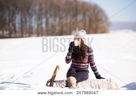 Beautiful young woman in knitted hat and gloves holding a cup of coffee outside in winter nature. Woman sitting on a sledge.