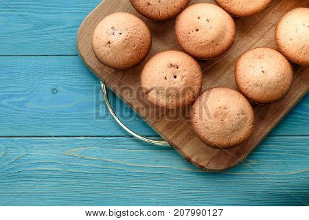 Fresh muffins on a cutting board on a wooden blue background. Background. Texture of freshly baked muffin. Close-up. Macro