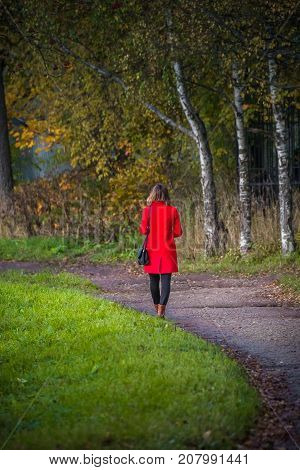 A girl in a red coat strolls in an autumn park. View from the back.