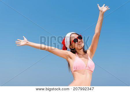 Christmas holiday beach fun vacation bikini asian woman running carefree splashing water enjoying freedom swim Caribbean travel paradise getaway with christmas santa hat. Sexy body model.