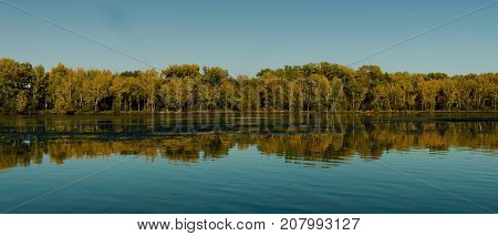 Autumn landscape. River and forest. Natural background. River. River background. Irtysh river. Blue sky and blue river.