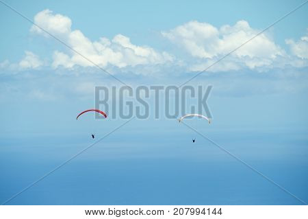 Red and white paragliders fly over Indian ocean with clouds at the background in Reunion island, France.