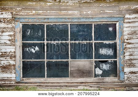 Grunge background scene of a large garage window on a weathered exterior wooden wall with 12 dirty windowpanes.