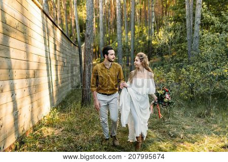 Newlyweds are walking in the forest. Girl in white dress and man in an olive shirt. Rustic wedding. Artwork., full length