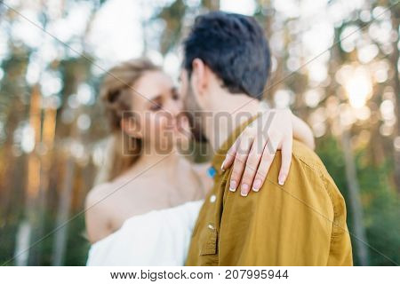Bride is embracing groom's back by her tender hand. Blurred newlyweds look at each other with tenderness and love. Close-up portrait. Artwork