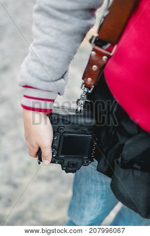 Photo camera on a leather strap. Photographer holds a camera in the hand. Close-up