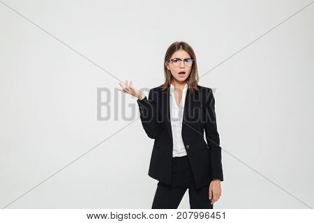 Portrait of a frustrated puzzled businesswoman in suit and eyeglasses pointing away at copy space isolated over white background