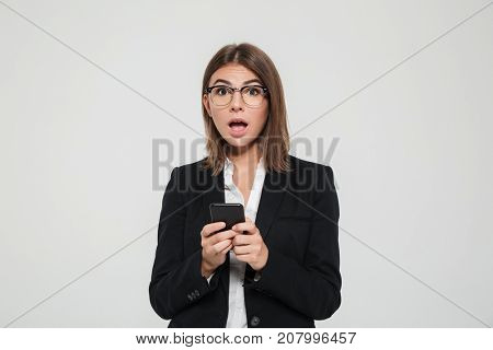 Taken by surprise young businesswoman in suit and eyeglasses holding mobile phone and looking at camera isolated over white background