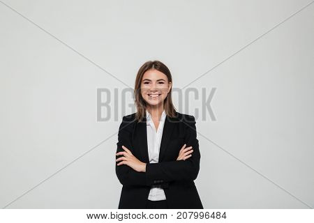 Portrait of happy pretty businesswoman in suit standing with arms folded and looking at camera isolated over white background