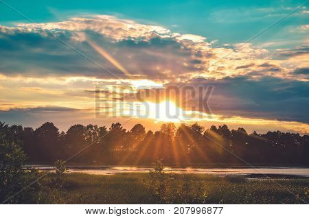 Beautiful afternoon landscape. Colorful sky and sunset over a rural pond.