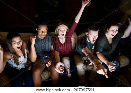 friends cheering while watching game on tv at night