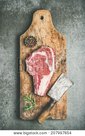 Flat-lay of raw prime beef meat dry-aged steak rib-eye on bone with seasoning and chopper on wooden cutting board over grey concrete countertop background, top view. Meat high-protein dinner concept