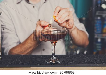 Professional bartender in bar interior making flaming alcoholic cocktail, burn it with lighter