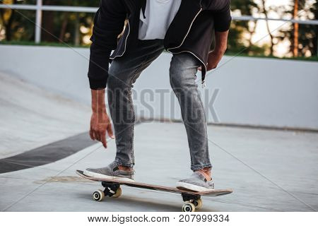 Cropped image of a young african male teenager riding on skateboard at a skate park