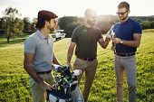 stylish multicultural friends spending time together while playing golf on golf course poster