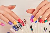 Manicured hands and polish color samples. Manicured hands touching nail sample with different design. Artificial nails on transparent basis. Varnish color palette for nails. poster