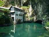 Dervish house and a cave nearby in a sunny summer day in Blagaj Bosnia and Herzegovina. Important monument of the early Ottoman period. River and house reflection. poster