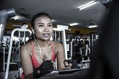 young sexy and sweaty Asian woman training hard at gym using elliptical pedaling machine gear in intense workout exercise wearing sport top and gloves in fitness and healthy lifestyle concept poster