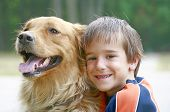 Little Boy Giving Golden Retriver a Hug Smiling poster