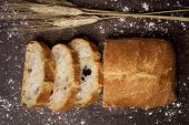 high-angle shot of some slices of pa de vidre or pa de coca, a bread typical of Catalonia, Spain, on a rustic wooden table poster