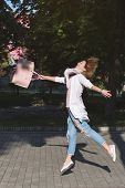 Jumping happy free woman in jeans with leather handbag outdoor. Easiness happiness concept. poster