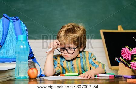 Clever, Education And Smart Learning Concept. Kid Boy Studying At School. Schoolboy Near Blackboard