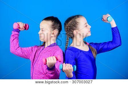Girls exercising with dumbbells. On way to stronger body. Beginner dumbbells exercises. Sporty upbringing. Children hold dumbbells blue background. Sport for teens. Easy exercises with dumbbell poster