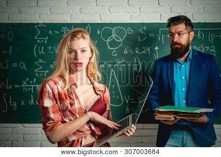 Sexy Gorgeous Blonde Woman Near Blackboard With Teacher Man. Sexology Teacher Looks At Sexy Female S