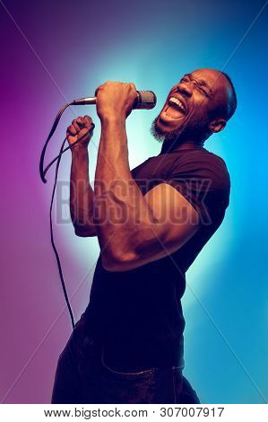 Young African-american Jazz Musician Singing A Song On Gradient Purple-blue Background. Concept Of M
