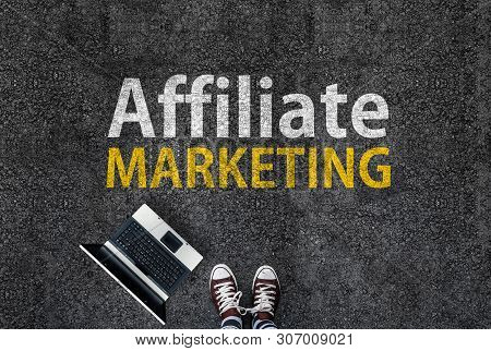 Affiliate Marketing. Man In Shoes Standing On Asphalt Next To Laptop And Affiliate Marketing Words