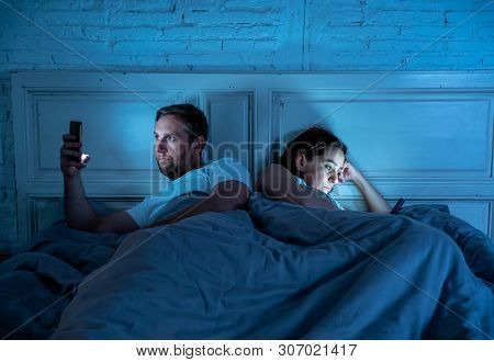 Sad And Bored Couple Addicted To Smart Mobile Phones Late At Night In Phase Of Mutual Disinterest