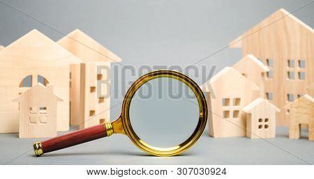 Magnifying Glass And Wooden Houses. House Searching Concept. Home Appraisal. Property Valuation. Cho