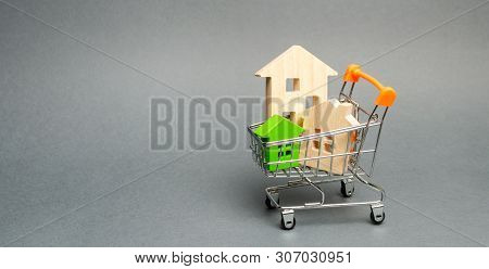 Wooden Houses In A Supermarket Trolley. The Concept Of Buying A House Or Apartment. Affordable Housi